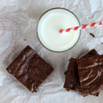 three chocolate protein brownies and a glass of milk with a straw