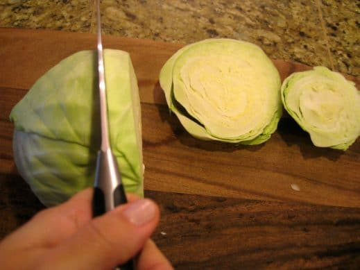 slicing a head of green cabbage into steaks