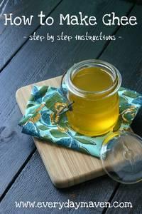 glass jar of liquid ghee on a wood cutting board with a blueish yellow napkin
