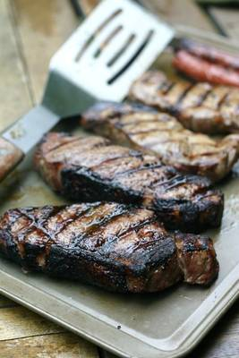 a tray of cooked strip steaks with grill marks and a large stainless steel spatula