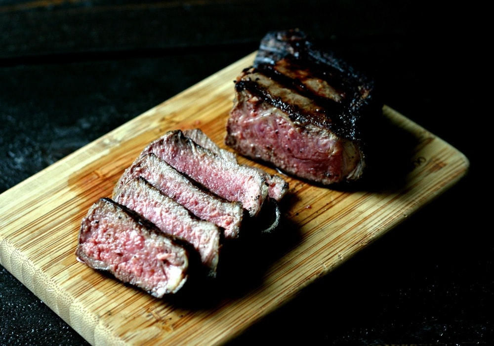 grilled steak cut into pieces on a wood cutting board