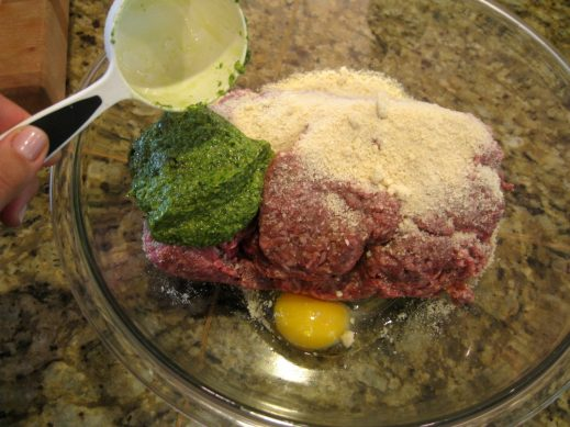mixing ingredients for pesto meatballs in a large glass mixing bowl