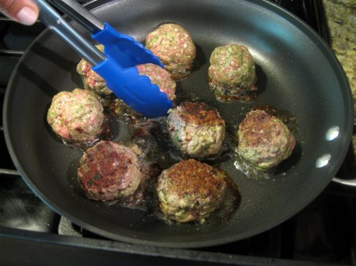 cooking pesto meatballs in a non-stick frying pan in batches