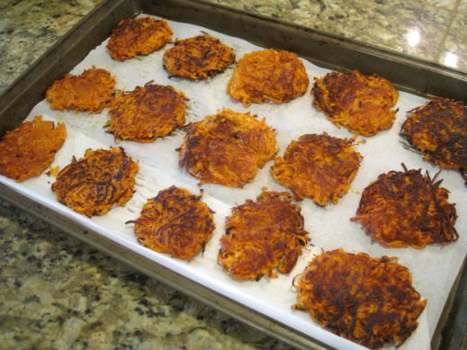 large baking sheet filled with cooked candied sweet potato latkes cooling on parchment paper