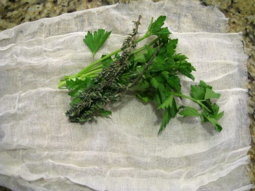 placing fresh herbs into a piece of cheesecloth to roll up for leftover turkey soup broth