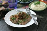 white dinner plate with cooked cube steak topped with fried onions and parsley