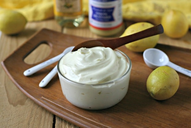 glass bowl of homemade mayonnaise in front of lemon, dijon mustard and other ingredients used on a wooden tray