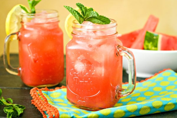 two mugs of watermelon cooler in front of a white bowl filled with watermelon slices