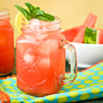 mason jar mug filled with watermelon vodka cocktail and topped with mint and lemon