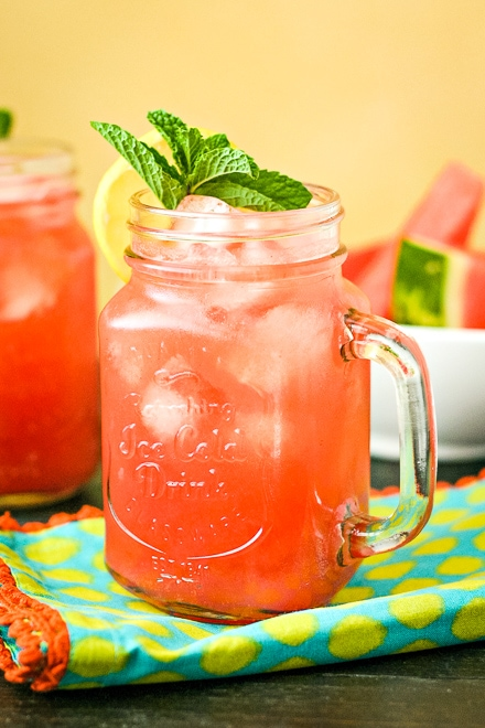 close up of watermelon cocktail topped with mint and lemon
