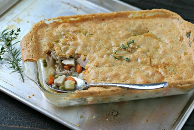 cooked pot pie in a pyrex style casserole dish on a baking sheet with fresh herbs