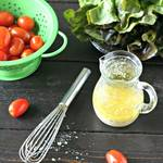 garlic salad dressing in a small glass canister on a wooden board with cherry tomatoes in a green colander, a head of red leaf lettuce and a small whisk