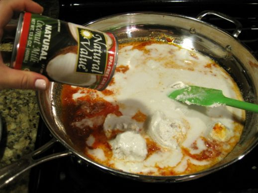 adding canned coconut milk to curry paste in a skillet for curry salmon recipe