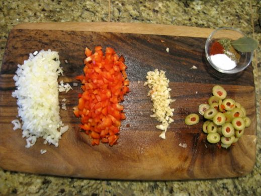 wood cutting board with choped onion, bell pepper, olives and spices for picadillo recipe