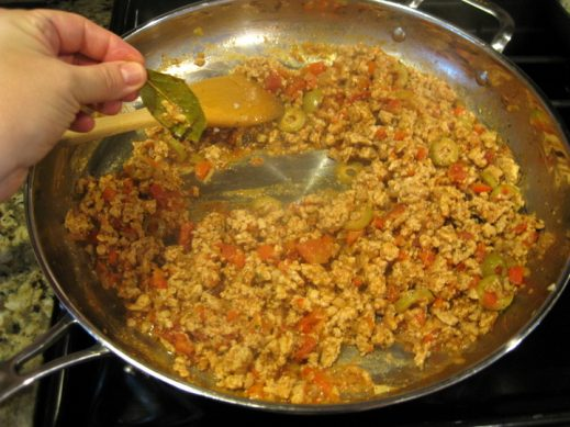 large frying pan with cooked ground chicken picadillo
