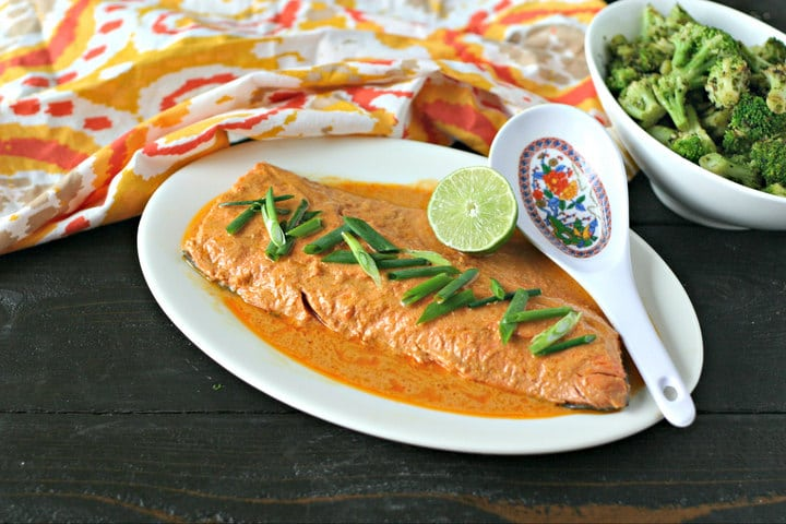 platter of cooked wild salmon with red curry sauce, lime and sliced scallions