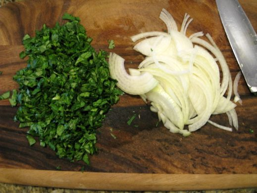 chopped cilantro and yellow onion on a wood cutting board for paprika chicken skillet