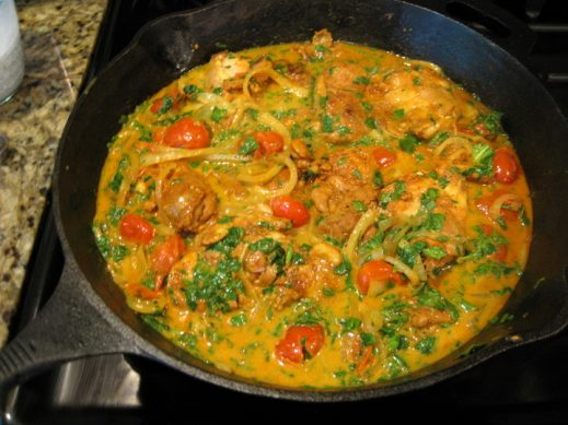 simmering chicken, vegetables and spices in coconut milk in a cast iron skillet