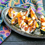 silver platter of roasted acorn squash with tahini drizzle