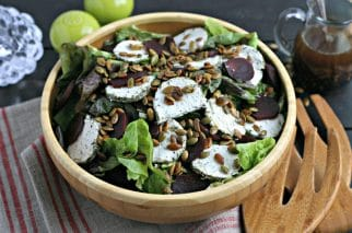 close up of wood salad bowl with thanksgiving salad topped with toasted pumpkin seeds