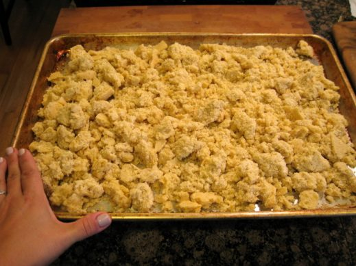 baking sheet with crumbled cornbread about to get toasted for cornbread sausage stuffing