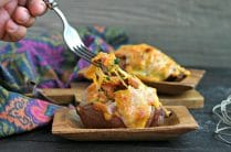 using a fork to dig into a loaded sweet potato topped with melted cheese
