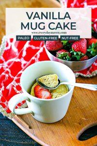 vanilla mug cake in a small mug with a spoon and strawberries