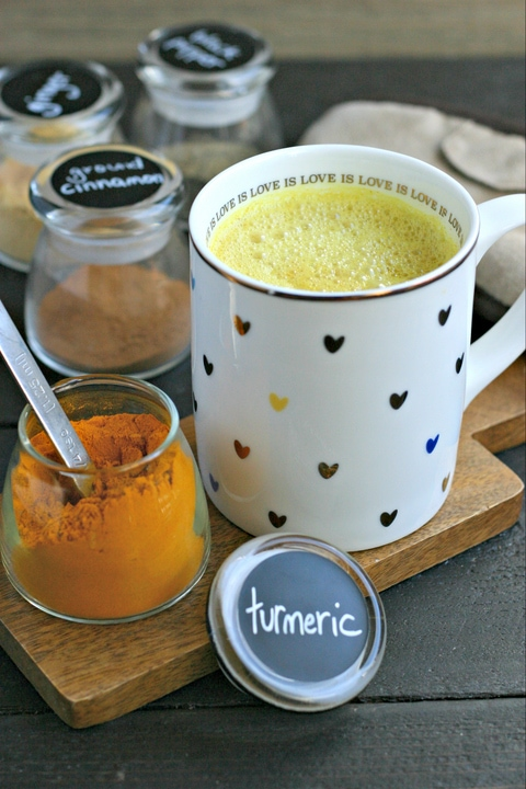 a mug of turmeric milk and dried spices to make the recipe