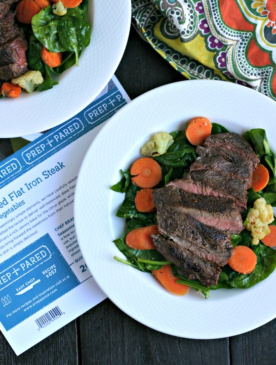 cooked flat iron steak and roasted vegetables on a white plate with recipe card and napkin