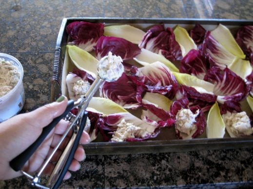 using a cookie scoop to spoon chicken salad into radicchio and endive cups on a serving tray