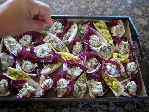 sprinkling fresh chopped dill over chicken salad stuffed radicchio and endive cups on a serving tray