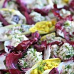 tray of chicken salad stuffed endive and radicchio leaves
