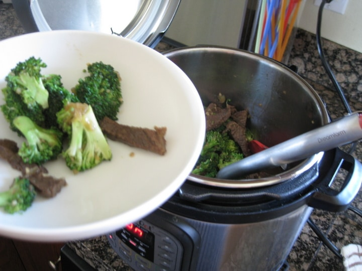 removing beef and broccoli with tongs to a white serving plate