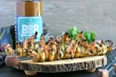 wood serving platter with shrimp skewers on top and bottle of bourbon in background
