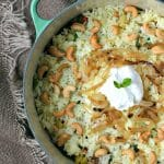 cooked vegetable biryani in a large pot topped with cashews and yogurt