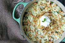 Green Le Creuset Pot with Veggie and Rice Biryani topped with cashews and yogurt