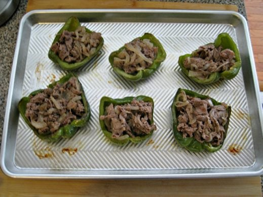 baking sheet with green bell peppers stuffed with philly cheesesteak meat and onions