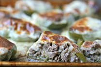 baking sheet with green bell pepper halves stuffed with philly cheesesteak meat and onions and topped with melted cheese