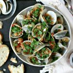 bowl of spicy steamed clams topped with lots of fresh parsley, served with crusty bread, a small bowl for the shells and a fringed napkin