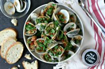 a white bowl of steamed clams in a spicy tomato sauce with crusty bread, red pepper flakes and a bowl for the shells