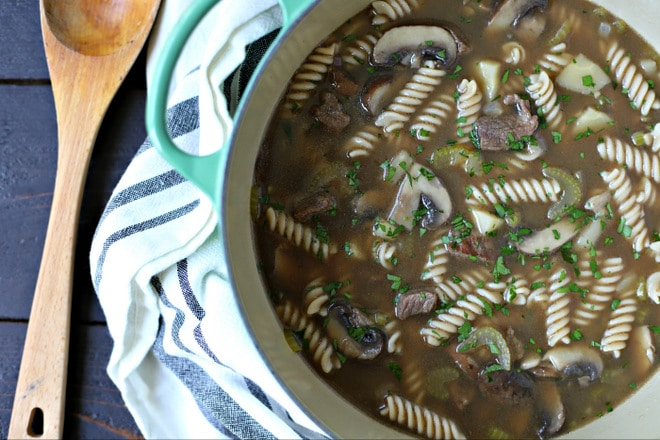 dutch oven filled with beef noodle soup sitting on a kitchen towel with a large wooden spoon