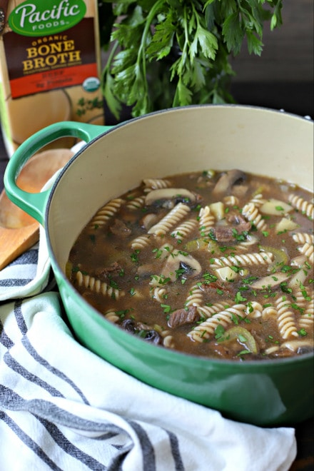 large pot of beef noodle soup with kitchen towel, wooden spoon and carton of beef bone broth
