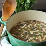 large pot of beef noodle soup with wooden spoon sticking out of side of pot. fresh parsley in the background