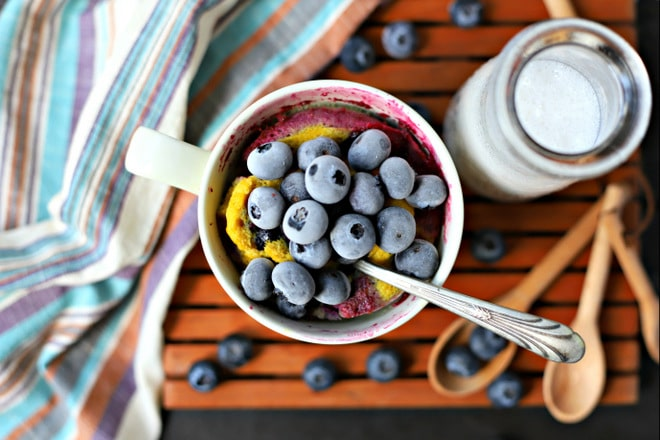 mug cake topped with blueberries, a glass of milk, measuring spoons and a striped napkin on a wood tray