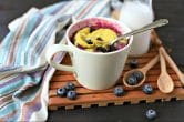 blueberry mug cake with silver spoon sticking out surrounded by fresh blueberries, a glass of milk and a napkin on a slotted wood tray