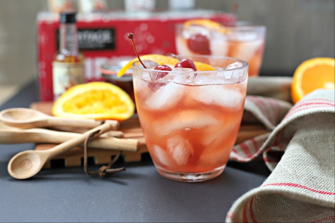 cherry manhattan in a short glass filled with ice and topped with cherries and orange twist