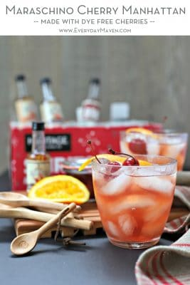 image of cherry manhattan in speckled glass in front of squeezed orange and wood measuring spoons