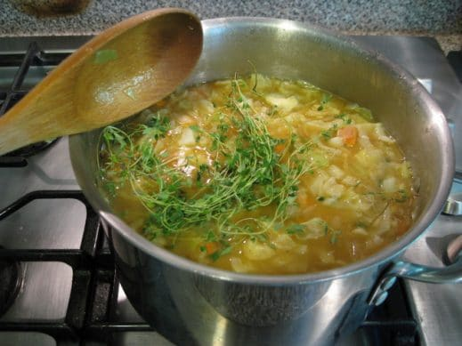 soup pot of vegetables with fresh thyme added in with a wooden spoon on the side