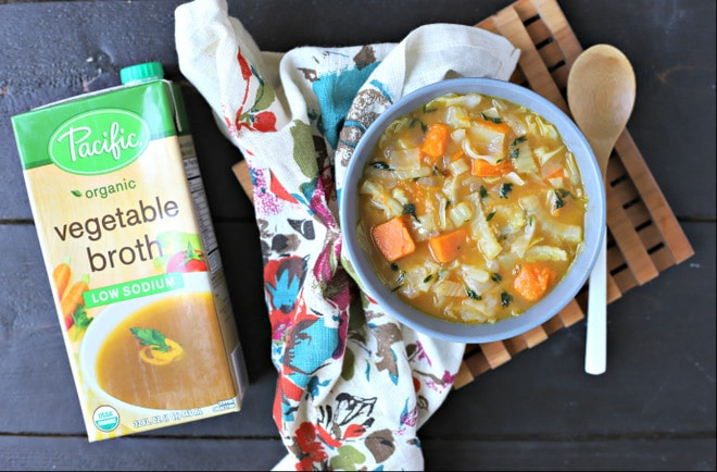 bowl of roasted vegetable soup on a floral linen with a box of Pacific Foods Organic Vegetable Broth