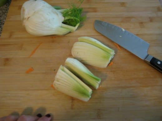 wood cutting board with quartered fennel about to be sliced with sharp knife